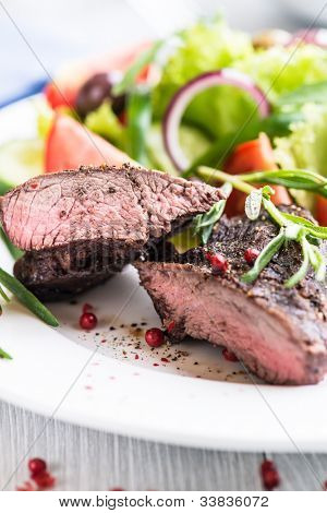 Beef steak with vegetable salad on a plate