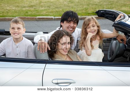 Family of four - parents and two children -  sits in a cabriolet, everybody smile.