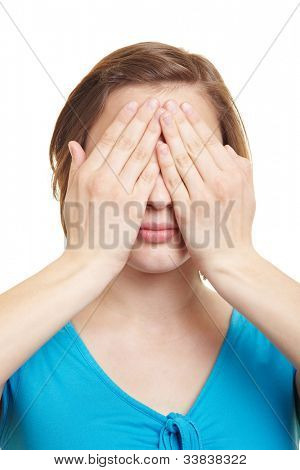 Young woman covering her eyes with both hands