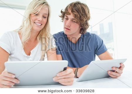 A curious man looking at the screen of his girlfriends tablet screen