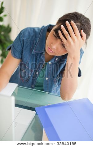 Student with a headache while doing her homework on her laptop