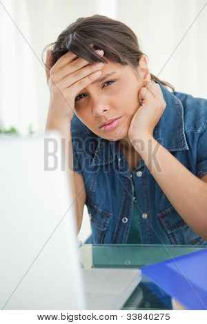 Portrait of a female student having a headache while doing her homework