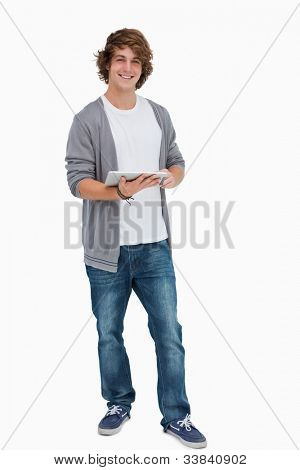 Male student posing while holding a touch pad against white background