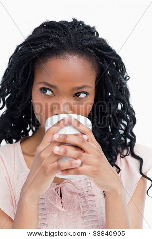 A close up shot of a woman who is drinking out of a cup