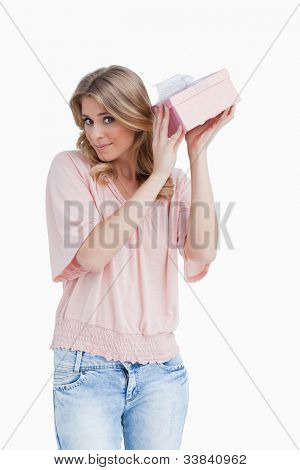 Peaceful young woman shaking her gift against a white background