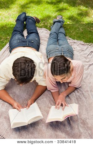 Elevated view of a man and a woman reading books while on a lying next to each other on a blanket in the grass