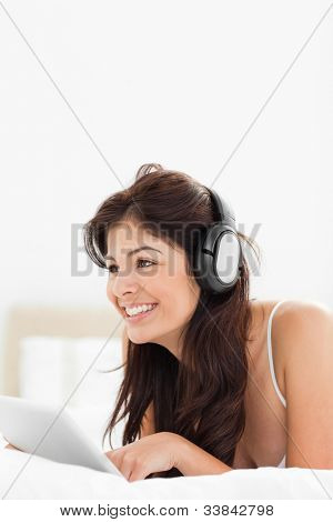 A woman using enjoying the use of her tablet and headphones while lying on the bed.