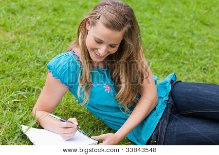 Young girl lying on the grass in a park while writing on a notebook and smiling