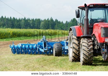 Ploughing heavy tractor during cultivation agriculture works at field with plough