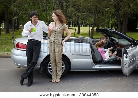 Parents stand near gig, talk and drink something from plastic cups, children play in the car