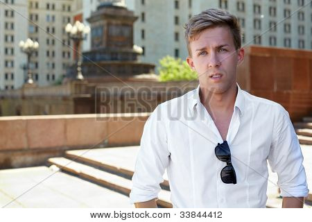 Young man stands on the steps of the architectural complex