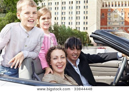 Family of four in cabriolet, children stand on backseats, parents sit on front seats, everybody laugh
