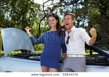 Young girl and her boyfriend stand leaning at car and show triumph gesture with their hands, boy shouts