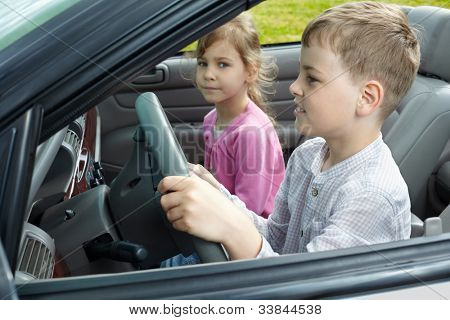 Boy sits on a driver seat in open top car and his sister sits on passenger seat, focus on boy, close-up.