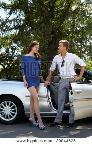 Young couple stands near cabriolet and talks