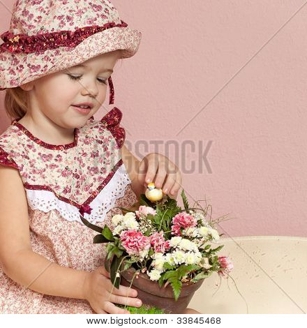 little child baby girl  indoors in babyroom smiling happy playing with flowers