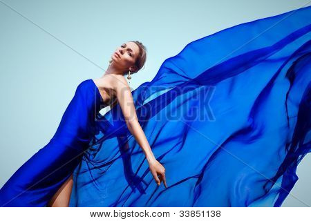 Photo of graceful female folded in dark blue chiffon shawl looking at camera