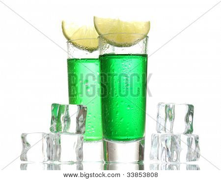 glasses of absinthe, ice and lime isolated on white