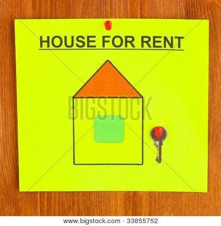 Poster über das Haus mit dem Schlüssel auf hölzernen Hintergrund mieten