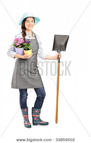 Full length portrait of a female worker holding a shovel isolated on white background