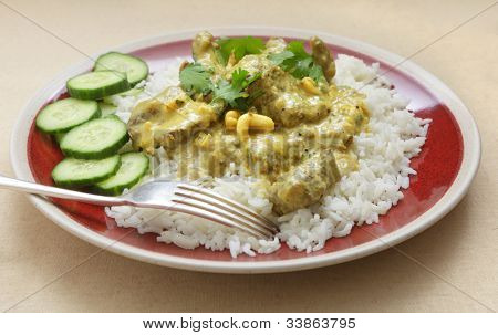 A British-style cream and coconut milk based beef korma curry, with cashew nuts, served with basmati rice, coriander garnish and sliced cucumber