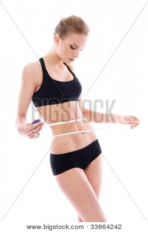 Beautiful woman measuring her waistline over white background