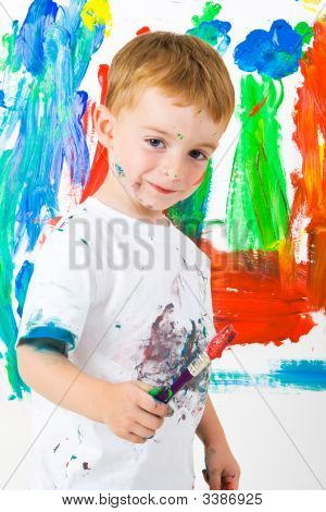 A Small Boy Painting A Wall With A Great Expression