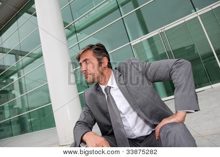 Businessman sitting in stairs in front of building