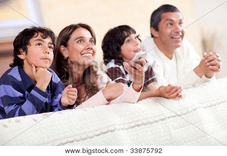 Happy family watching tv together and lying in bed