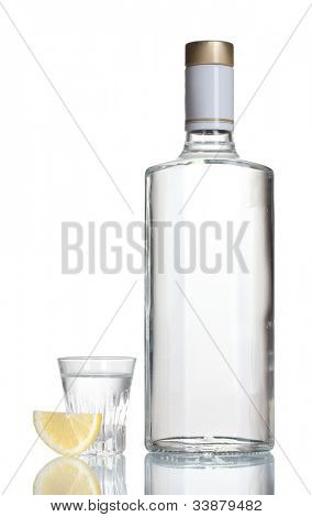 Bottle of vodka and wineglass with lemon isolated on white