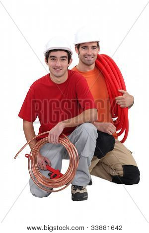Plumbers with traditional copper and modern plastic pipe