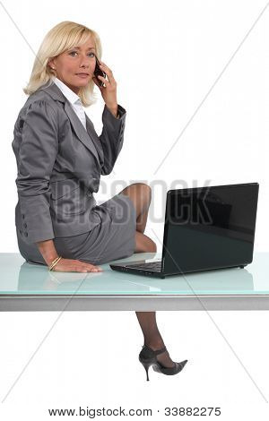 Blond executive sat on desk making call