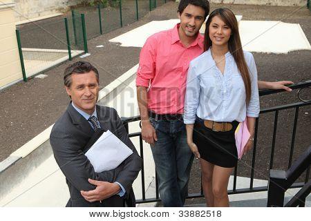 Agente imobiliário e o jovem casal ficou fora Propriedade