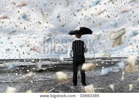 Young businessman standing with umbrella under money rain