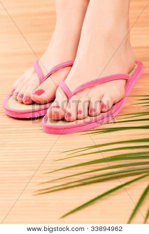Pés femininos em sandálias cor de rosa