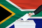 Election In South Africa. The Hand Of Man Putting His Vote In The Ballot Box. Waved South Africa Fla poster