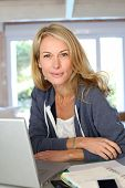 pic of middle-age  - Middle aged blond woman working at home with laptop - JPG