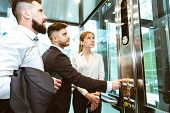 Business Team Group Going On Elevator. Business People In A Large Glass Elevator In A Modern Office. poster