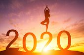 Happy New Year 2020, Silhouette Woman Practicing Yoga Early Morning Sunrise Over The Horizon Backgro poster