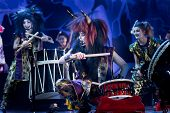 Traditional Japanese Performance. Taiko Drummers In A Wigs And A Demon Masks Perform On Stage With D poster