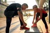 Healthy Family. Active Middle-aged Couple In Sports Clothing Tying Shoelaces Before Jogging Outdoors poster