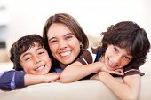 stock photo of tickling  - Happy mother with her two sons smiling at home - JPG