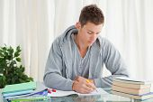 image of midterm  - Male student doing his homework in his house - JPG