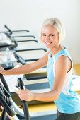 Fitness young woman on elliptical cross trainer at health gym