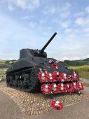 Sherman tank at Slapton Sands, Devon,UK covered in red poppy wreaths commemorating D Day landings in poster