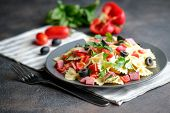 Traditional Salad With Pasta Farfalle, Ham, Pepper And Herbs On A Dark Plate On A Dark Background To poster