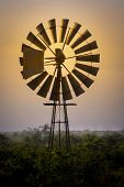 Old-fashioned And Low Tech Waterpump Windmill In Rural Farm Area Against A Dramatic Sunset With Oran poster