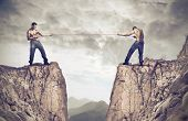stock photo of tug-of-war  - Two young men playing tug of war over a precipice - JPG