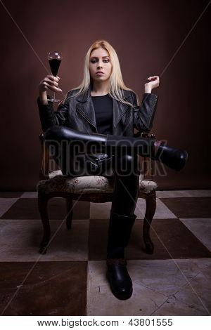 Woman In Leather Jaket Sitting On A Vintage Chair With A Glass Of Liquid In Hands