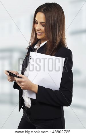 Business Woman Sending Text Message On Mobile Phone At Office